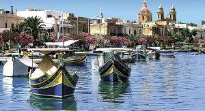 """Bilderbuch-Malta: Fischerboote vor Marsaxlokk mit der """"Our Lady of Pomei""""-Kirche"""