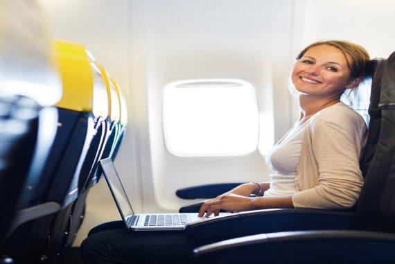 Frau im Flieger mit Laptop