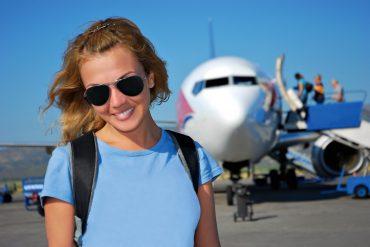 Frau mit Sonnenbrille vor Flugzeug