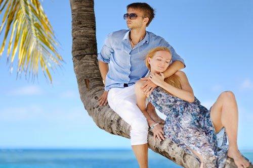 Paar sitzt auf einer Palme