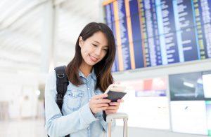 Frau am Flughafen mit mobilem Endgerät